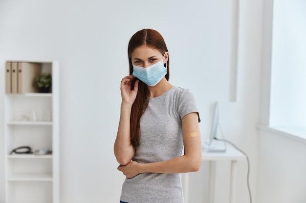 Gesso germicida no ombro de uma mulher usando máscara médica em um passaporte secreto de hospital