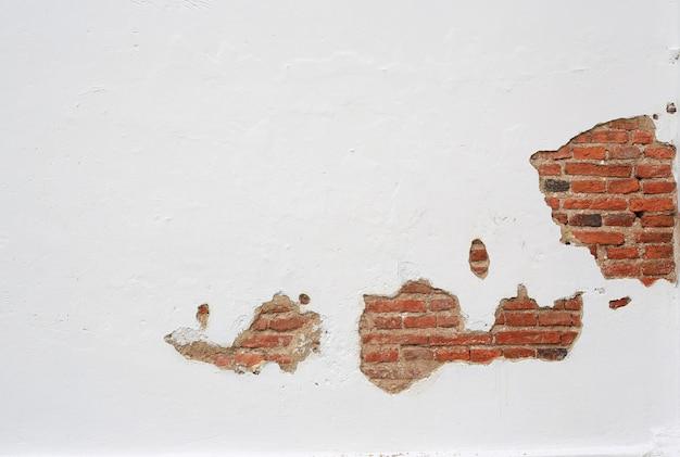 Gesso rachado da velha parede de tijolos