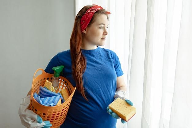 Gestante com cesta de produtos para limpeza e manutenção da casa.