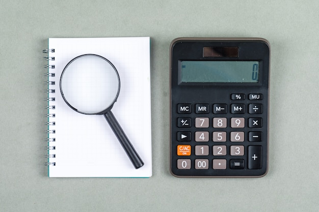 Gestão de tempo e conceito da pesquisa com caderno, lente de aumento, calculadora na opinião superior do fundo cinzento. imagem horizontal