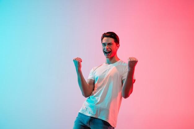 Gesticulando. retrato de jovem caucasiano em estúdio gradiente azul-rosa em luz de néon