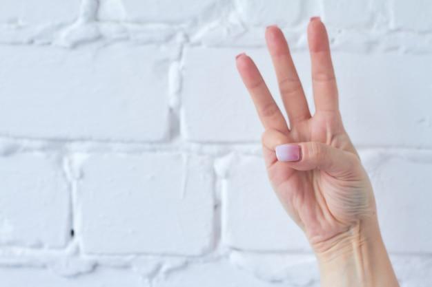 Gesto com a mão isolado no fundo da parede de tijolo branco