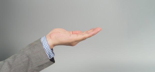 Gesto com a mão vazia em terno cinza em fundo cinza. tópico do empresário. feche a foto e o tiro do estúdio.