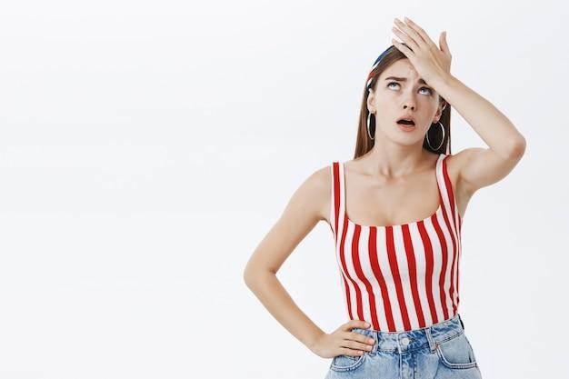 Gesto com a palma da mão. retrato de uma jovem arrogante, infeliz e irritada, usando uma blusa listrada, aplaudindo a face com irritação, expirando com a boca aberta e olhos revirados