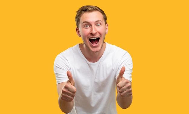 Gesto como. admiração de aprovação. homem animado apoiando com polegares para cima isolados em fundo laranja.