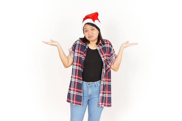 Gesto confuso de linda mulher asiática vestindo camisa xadrez vermelha e chapéu de papai noel isolado no branco