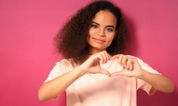 Gesto de amor com um olhar terno e bela jovem olhando positivamente para a frente usando uma camiseta cor de pêssego isolada na parede rosa