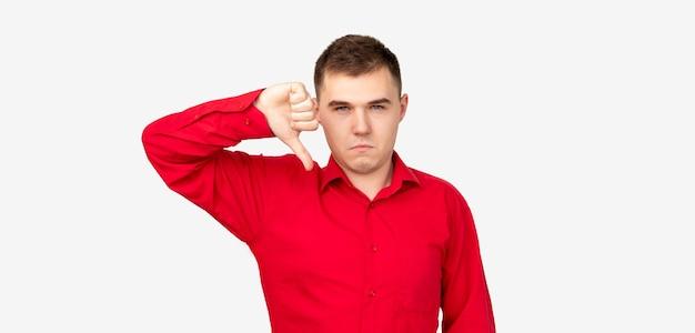 Gesto de antipatia. péssima ideia. homem cético de camisa vermelha, mostrando o polegar isolado no fundo branco.