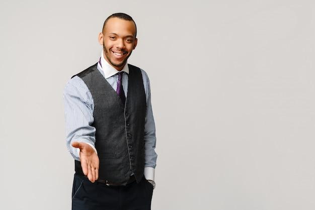 Gesto de aperto de mão bonito empresário afro-americano sobre parede cinza claro.