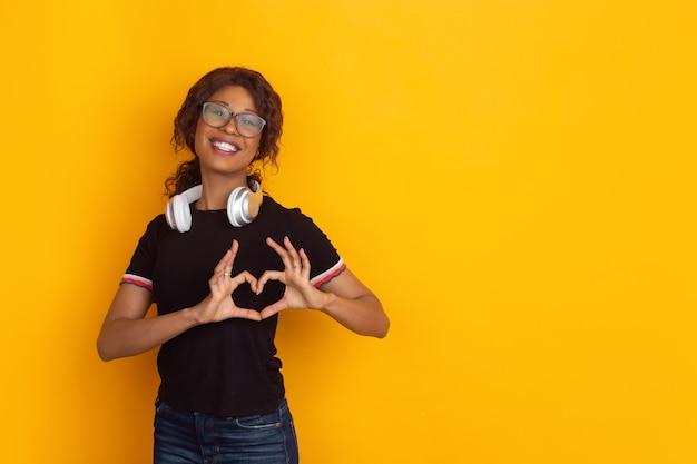 Gesto de coração com as mãos. retrato de uma jovem afro-americana isolado no fundo amarelo do estúdio. lindo modelo feminino encaracolado. conceito de emoções humanas, expressão facial, vendas, anúncio, juventude.