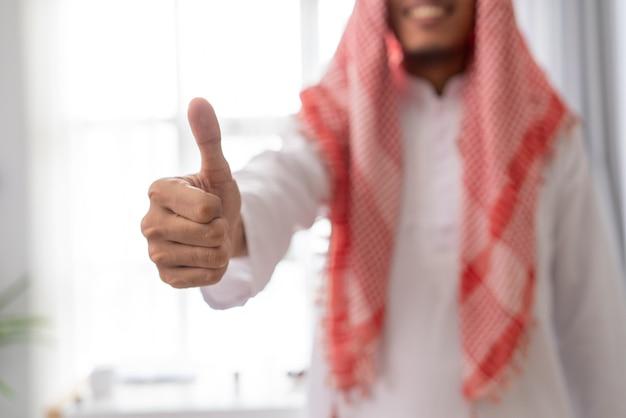 Gesto de empresário muçulmano árabe em pé aparecendo o polegar