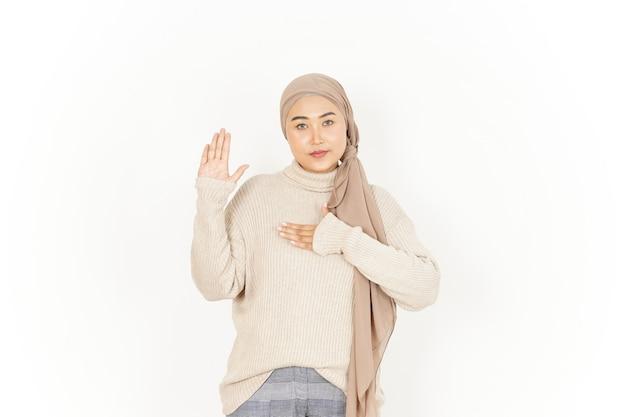 Gesto de juramento, faça um juramento de uma bela mulher asiática usando um hijab isolado no fundo branco