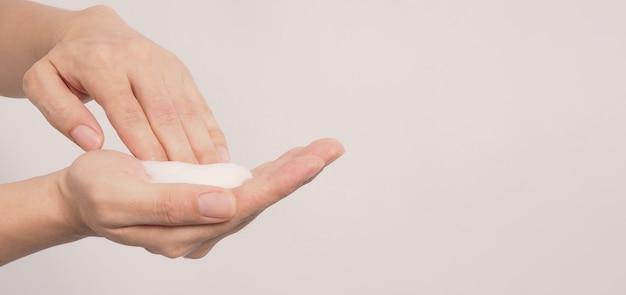 Gesto de lavagem das mãos com espuma de sabão para as mãos e bolhas em fundo branco.