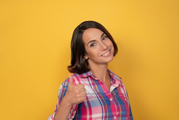 Gesto de levantar o polegar para cima com sorriso de mão. mulher bonita vestida com uma camisa xadrez e cabelo escuro na parede amarela