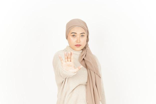 Gesto de parada ou rejeição de uma linda mulher asiática usando um hijab isolado no fundo branco