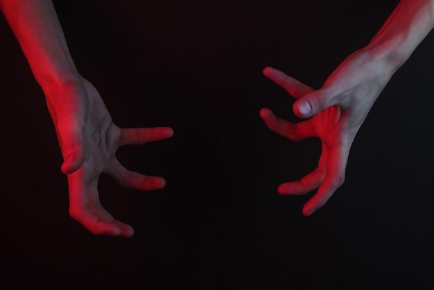 Gesto incrível de mãos femininas em um fundo preto. conceito de halloween. luz neon vermelha
