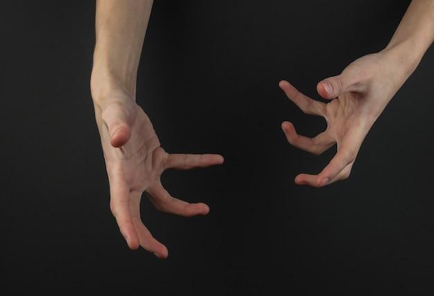 Gesto incrível de mãos femininas em um fundo preto. conceito de halloween.