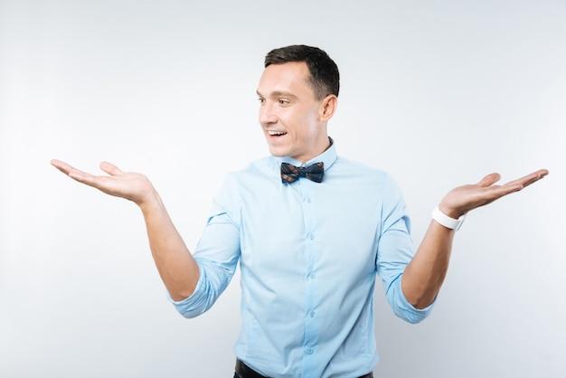 Gesto interessante. homem atraente positivo e encantado sorrindo e olhando para sua mão, mantendo-a em uma posição interessante