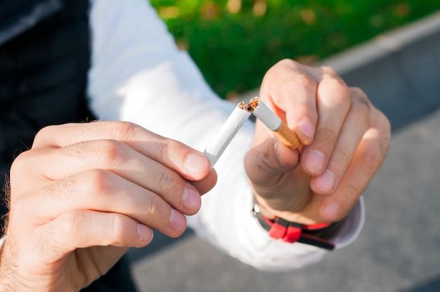 Gesto para parar de fumar, anti-fumaça, cigarro macho esmagador de mão, não fumadores. o homem decidiu parar de fumar.