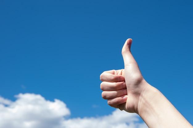 Gesto, polegar para cima em um fundo de céu azul e nuvens, copie o espaço