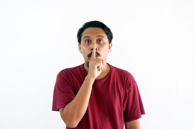 Gesto silencioso homem asiático enquanto olha para a câmera