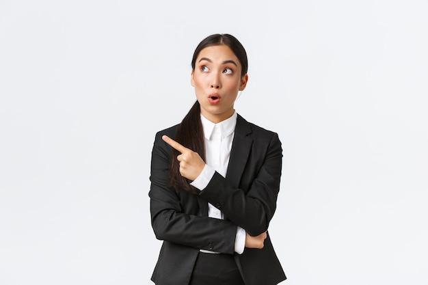 Gestora asiática muito impressionada, empresária de terno apontando e olhando para o canto superior esquerdo com expressão de espanto, bom negócio local, fundo branco de pé