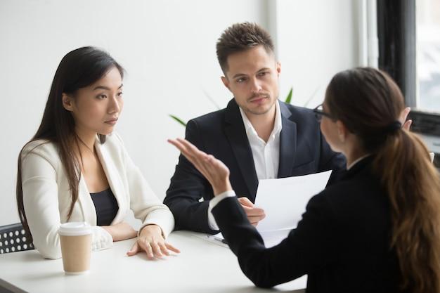 Gestores de rh diversificados céticos entrevistando candidata do sexo feminino, primeira impressão ruim