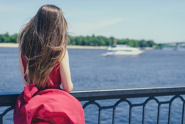 Getawaylove da cidade da aventura da nuvem do céu desfrutar do conceito de felicidade único e solitário. retrato de uma moça bonita vestida de vermelho com cabelo comprido, olhando para o oceano. estilo de vida de lazer