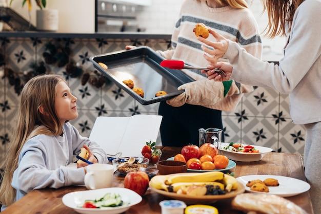 Ggirl na mesa da cozinha faz sua lição de casa enquanto os adultos arrumam a mesa para o jantar.