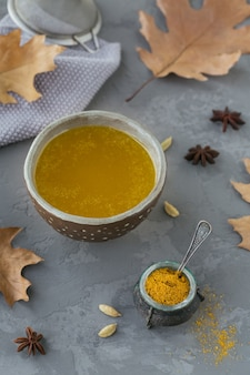 Ghee caseiro saudável ou manteiga clarificada em uma jarra e açafrão em pó na mesa de concreto cinza