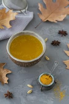 Ghee caseiro saudável ou manteiga clarificada em uma jarra e açafrão em pó na superfície de concreto cinza