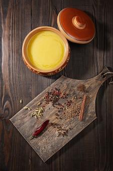 Ghee em uma panela de cerâmica e um conjunto de especiarias para a preparação de garam masala indiano. vista do topo.