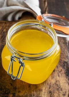 Ghee ou manteiga derretida em um pote na mesa de madeira.