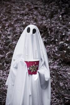 Ghost segurando caixa de pipoca com grãos caindo