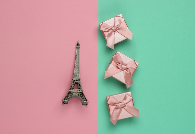 Gift boxex com arco, estatueta da torre eiffel em fundo rosa azul pastel. compras em paris, souvenirs. vista do topo