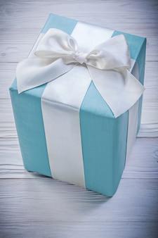 Giftbox azul no conceito de celebrações de vista superior da placa de madeira