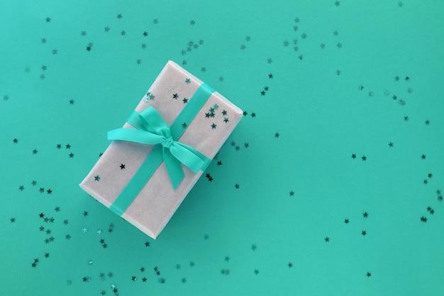Giftbox com enfeites de fita e confetes em fundo colorido de papel pastel. camada plana, vista superior, espaço de cópia