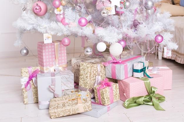 Giftboxes, bolas de decorações de natal-de-rosa e branco pendurado em uma árvore de natal branca decorativa