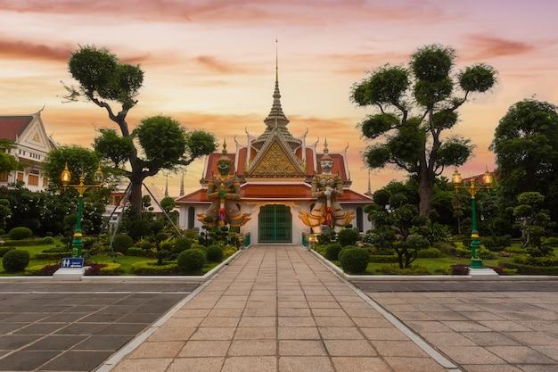 Gigante na frente do templo de buda (wat arun) no distrito de bangkok yai de bangkok, tailândia, na margem oeste de thonburi do rio chao phraya.