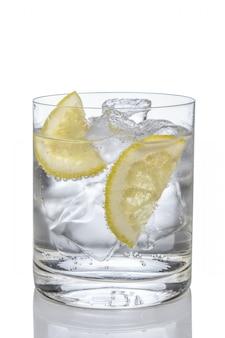 Gim e tónico do cocktail com o limão e o gelo isolados no branco.