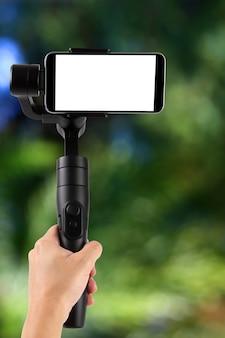 Gimbal. jovem usando estabilizador para celular e filmando a floresta. foco seletivo