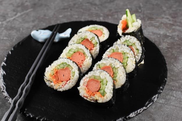 Gimbap de rolo coreano (kimbob ou kimbap) feito de arroz branco cozido no vapor (bap) e vários outros ingredientes, como kyuri, cenoura, salsicha, pau de caranguejo ou kimchi e embrulhado com lavadora de algas marinhas