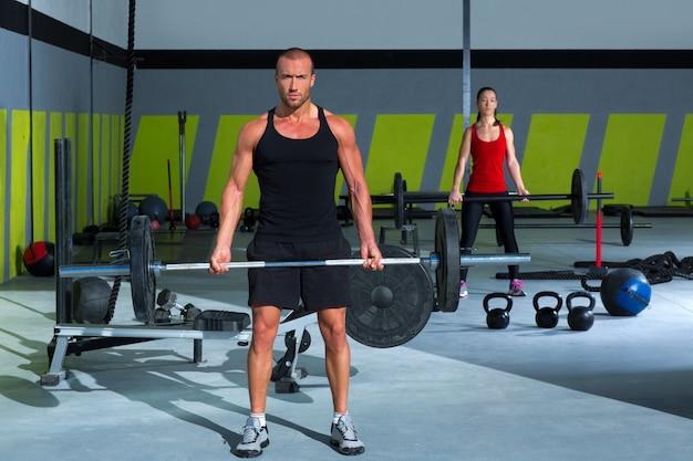 Ginásio com barra de levantamento de peso treino homem e mulher