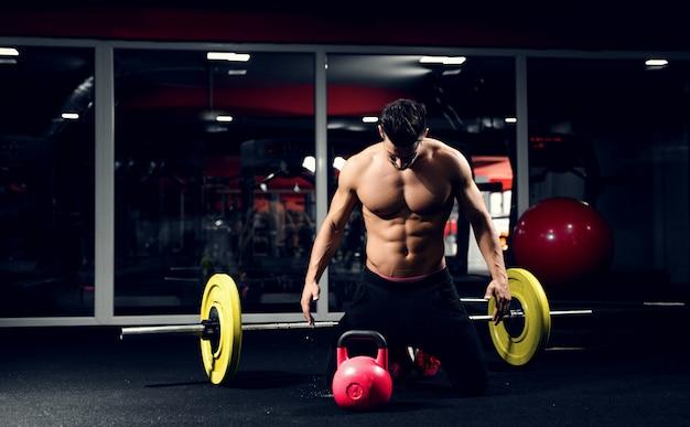 Ginásio de construtor do corpo se preparando para o treino. sino de chaleira halterofilista.
