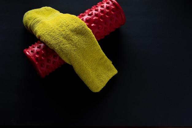 Ginásio de rolos vermelhos e toalhas verdes em um fundo preto de ginástica doméstica