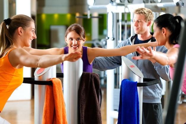 Ginásio - mulheres e treinador frente da máquina de exercício