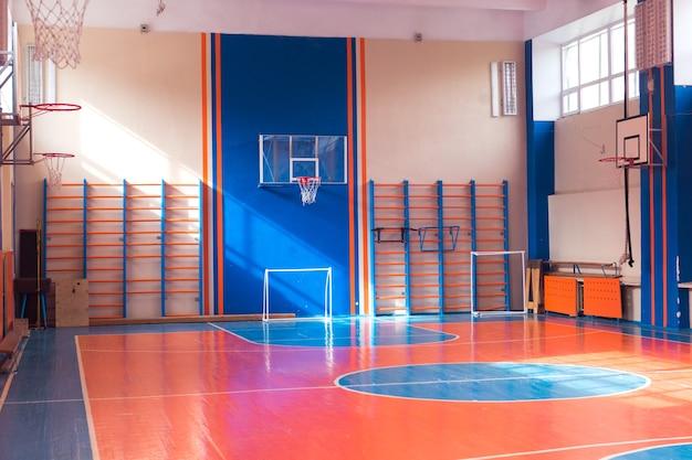 Ginásio vazio no basquete universitário e campo de futebol