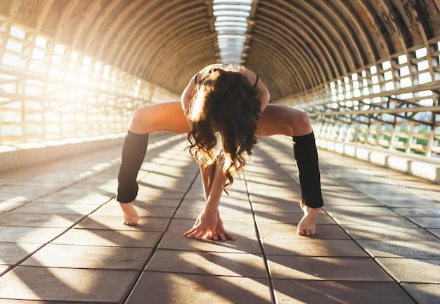 Ginasta de dançarina de rua jovem morena esbelta senta-se em pose de divisões na ponte de rua