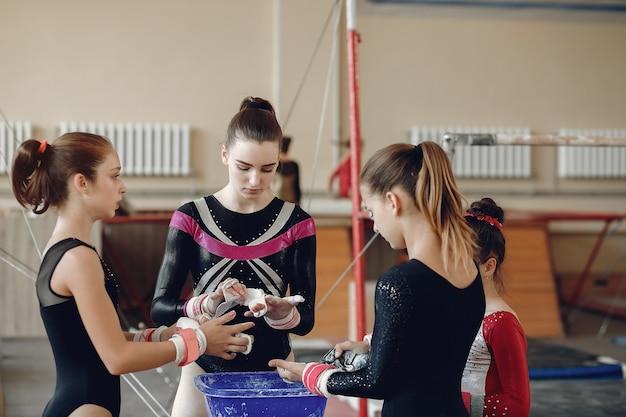 Ginasta de meninas em apertos de mão de ginástica manchando o giz de ginástica. crianças em uma escola de atletismo.