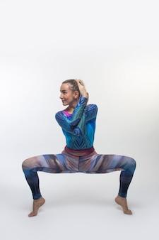 Ginasta em uma meia-calça multicolorida durante alongamento
